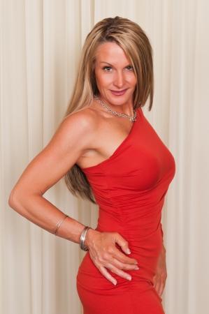 Beautiful mature blonde in a red dress photo