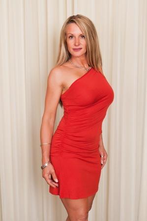 赤いドレスを着た美しい成熟した金髪