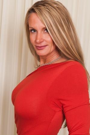 donne mature sexy: Bella bionda matura in un abito rosso Archivio Fotografico