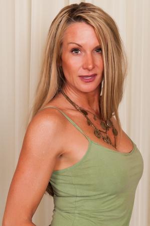 탱크 탑: Beautiful mature blonde in a green tank top 스톡 사진
