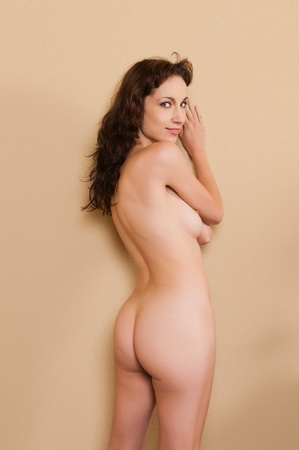 undressed young: Pretty slender brunette standing nude against a wall