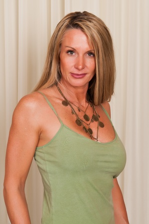 blouse sexy: Beautiful mature blonde in a green tank top Stock Photo