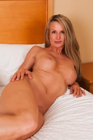 femme se deshabille: Belle blonde mature gisant nu au lit