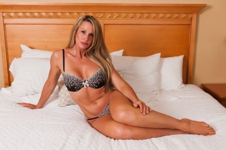 rubia: Hermosa rubia madura en la cama en ropa interior marr�n