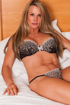 undergarment: Beautiful mature blonde in bed in brown lingerie Stock Photo