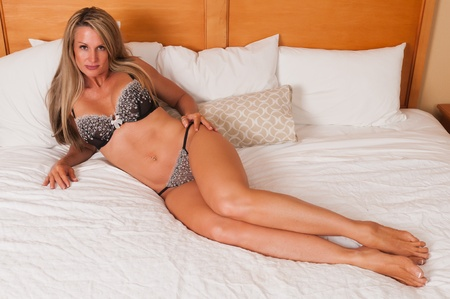 strong: Beautiful mature blonde in bed in brown lingerie Stock Photo