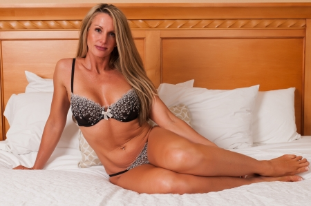 Beautiful mature blonde in bed in brown lingerie Stock Photo - 10420696