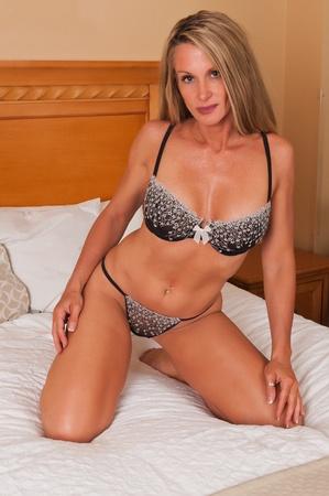 mujeres maduras: Hermosa rubia madura en la cama en ropa interior marr�n