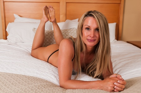 sexy bedroom: Beautiful mature blonde in bed in brown lingerie Stock Photo