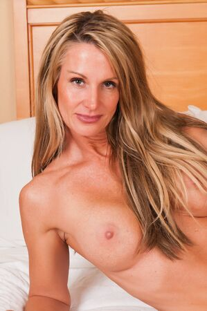 Beautiful mature blonde sitting nude in bed photo