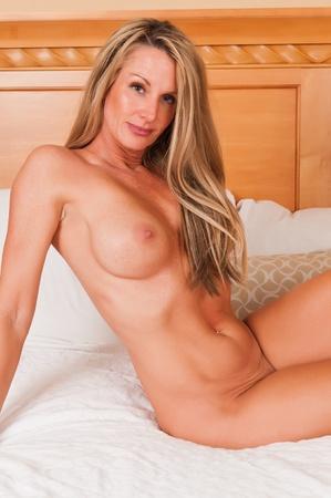 nudity: Beautiful mature blonde sitting nude in bed