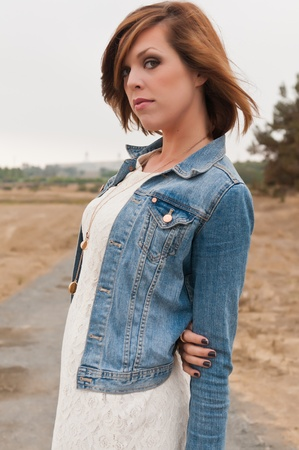 Tall pretty brunette in a white dress and denim jacket Фото со стока