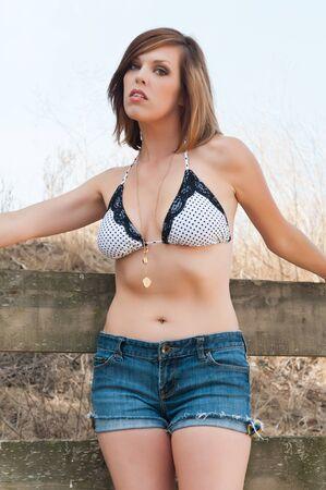 Tall pretty brunette in a bikini top and denim shorts photo
