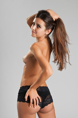 Pretty slender Romanian brunette topless in black panties Stock Photo - 10614386