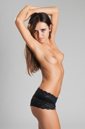 Pretty slender Romanian brunette topless in black panties Stock Photo - 10614310