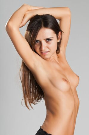 Pretty slender Romanian brunette topless in black panties Stock Photo - 10614388