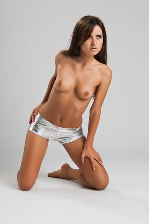 Pretty slender Romanian brunette topless in booty shorts Stock Photo - 10614409
