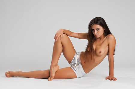 Pretty slender Romanian brunette topless in booty shorts Stock Photo - 10614411