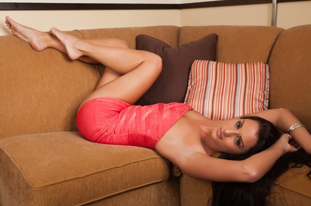 couches: Beautiful tall brunette in a short orange dress