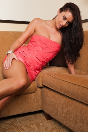 Beautiful tall brunette in a short orange dress photo