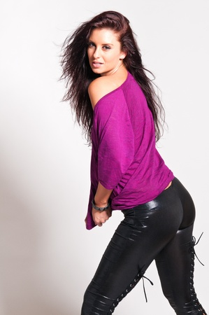 Beautiful tall brunette in a purple tee and black leather pants photo