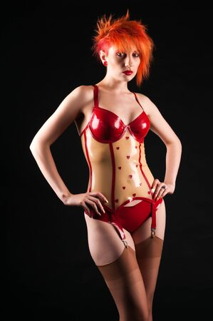 Pale slender redhead in latex fetish attire photo