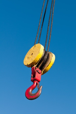 A pulley and hook hoist mechanism hanging from a crane