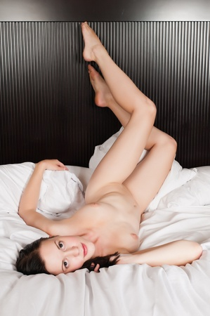 Pretty slender brunette lying in bed Stock Photo - 10908389