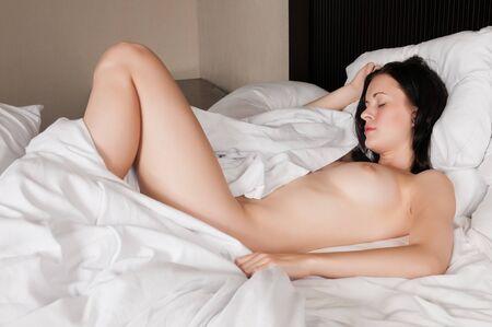 Pretty slender brunette lying in bed