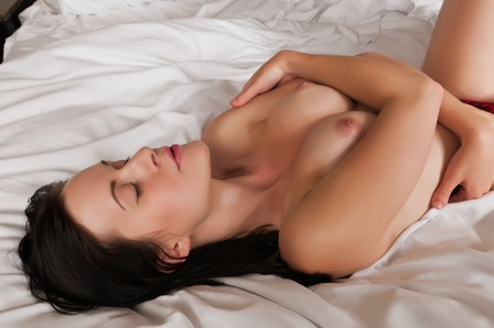Pretty slender brunette lying in bed Stock Photo - 10945803