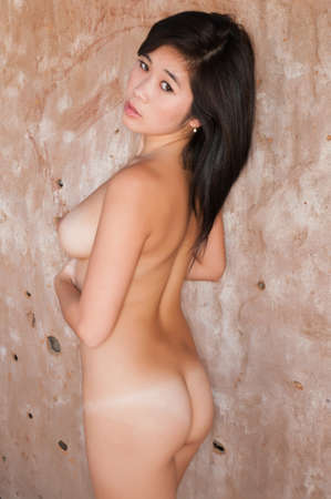 black women naked: Pretty young Laotian woman nude against an adobe wall