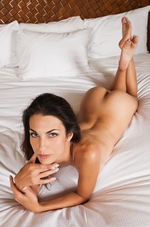 femme se deshabille: Belle brunette mince gisant nu au lit Banque d'images