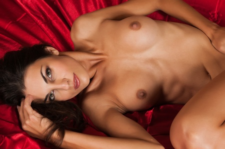 undressed young: Beautiful slender brunette lying nude in bed Stock Photo