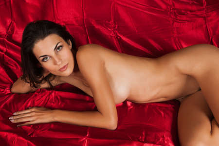Beautiful slender brunette lying nude in bed Stock Photo - 11051311