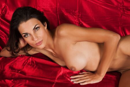 Beautiful slender brunette lying nude in bed Stock Photo - 11051315