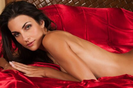 sexy naked girl: Beautiful slender brunette lying nude in bed Stock Photo