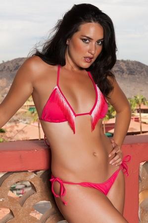 Pretty young brunette in a red bikini photo