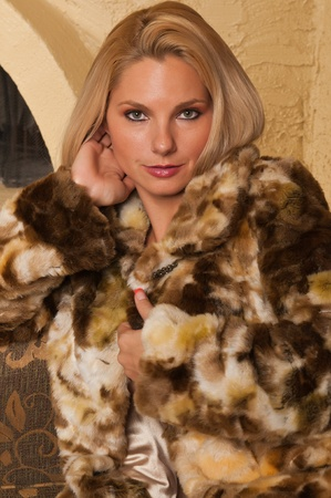 couches: Pretty blonde sitting on a couch in a fur coat Stock Photo