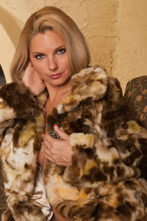 bontjas: Mooie blonde zittend op een bank in een bontjas
