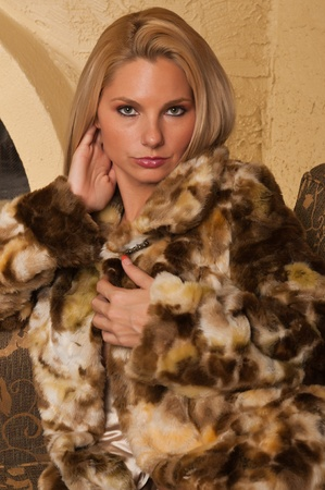Pretty blonde sitting on a couch in a fur coat Imagens - 11121482