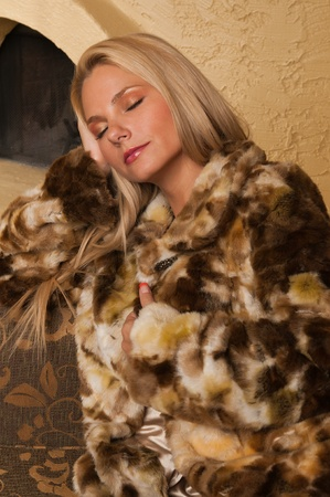woman on couch: Pretty blonde sitting on a couch in a fur coat Stock Photo