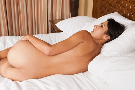 nude in bed: Beautiful slender brunette lying nude in bed Stock Photo