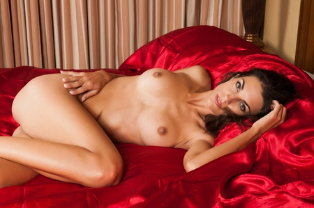 Beautiful slender brunette lying nude in bed Stock Photo - 11121733
