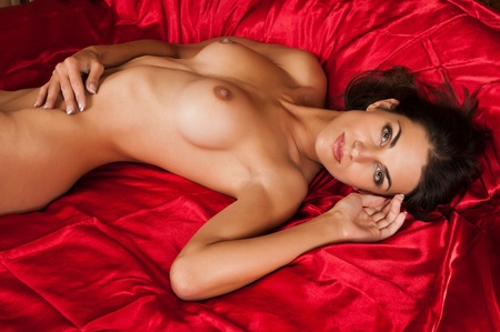 femme se deshabille: Belle brune �lanc�e nue couch�e dans le lit Banque d'images