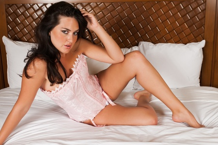 Pretty young brunette in bed in a pink corset photo