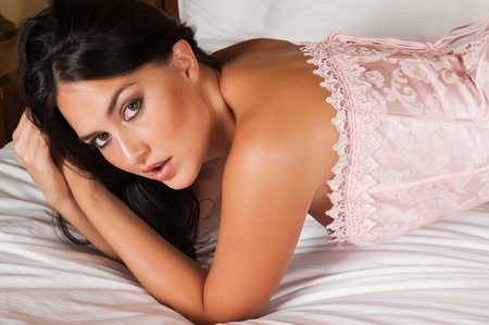 light blue lingerie: Pretty young brunette in bed in a pink corset Stock Photo