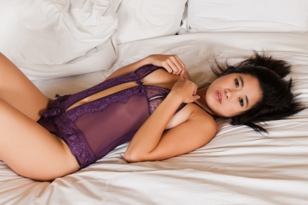 petite: Pretty young Laotian woman in purple lingerie Stock Photo