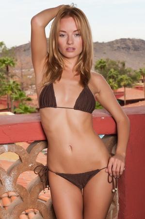 bikini slender: Lovely young blonde in a brown knit bikini