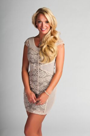 Pretty young blonde in a cream colored dress photo
