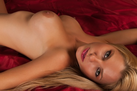 Pretty blonde woman lying nude on red sheets Stock Photo - 11232415